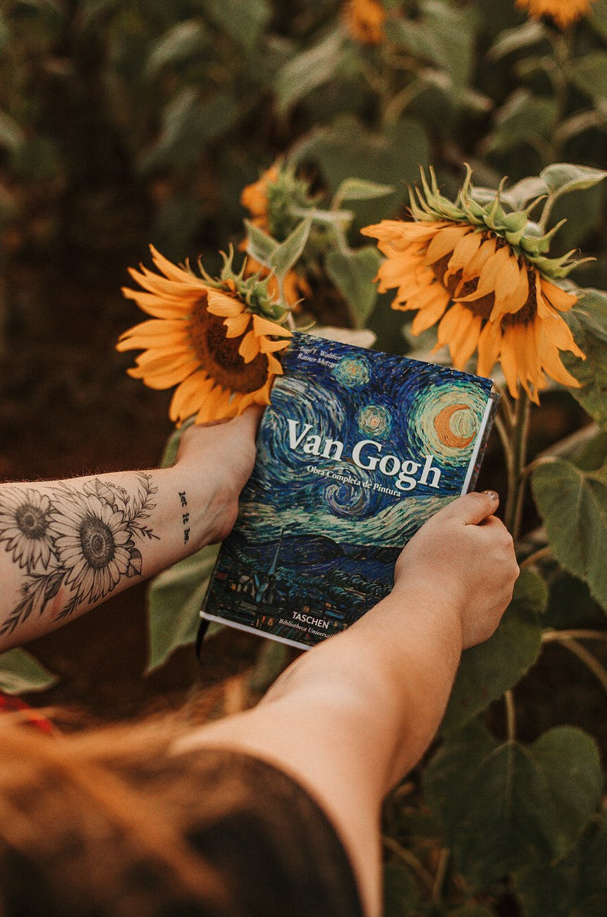 person holding van gogh book beside sunflowers
