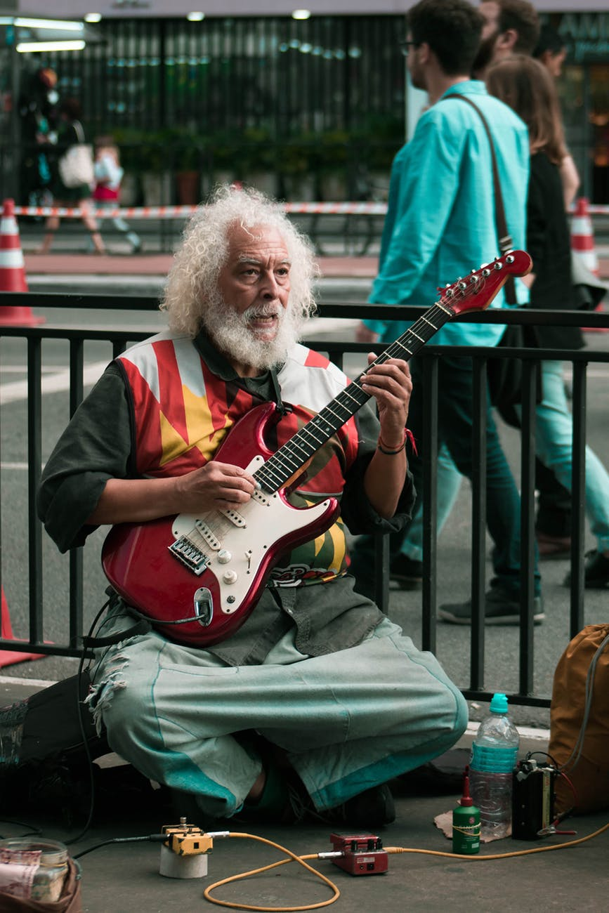man playing red and white electric guitar