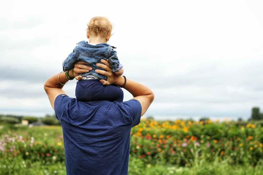 baby sitting on man s shoulder