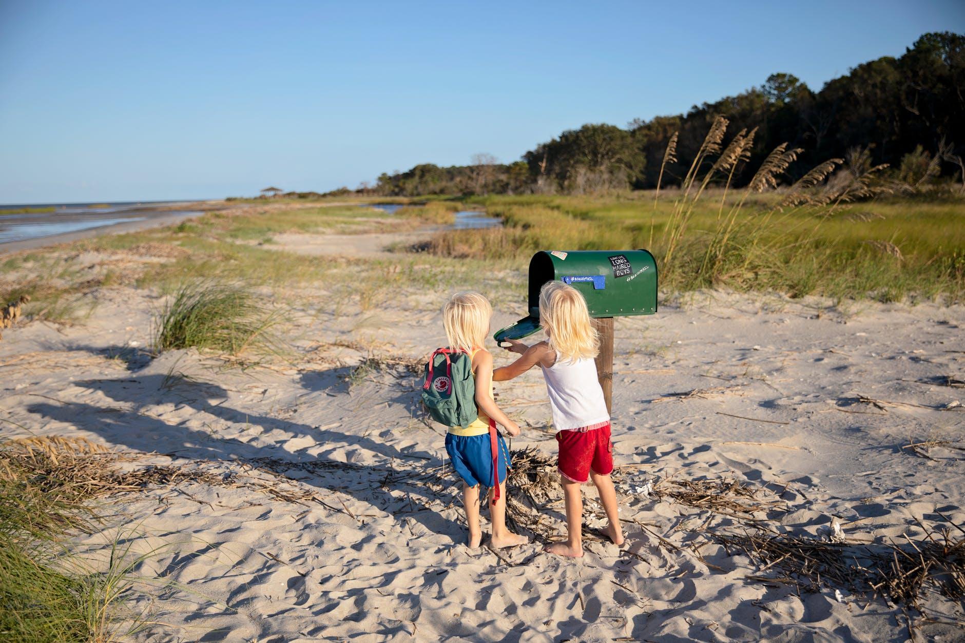 two children standing beside green mailbox