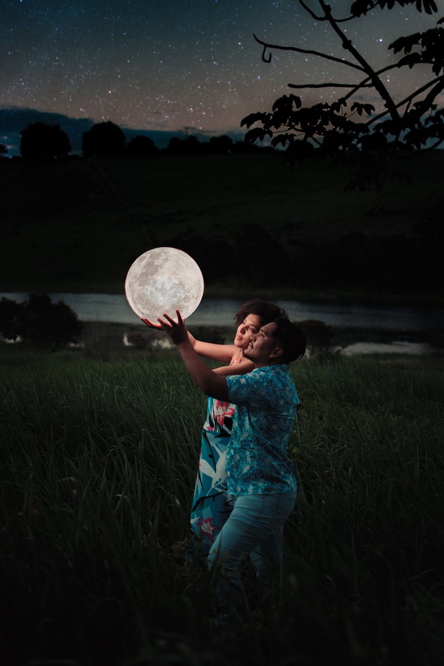 man and woman holding up a moon like illuminated spherical ball outdoor at night