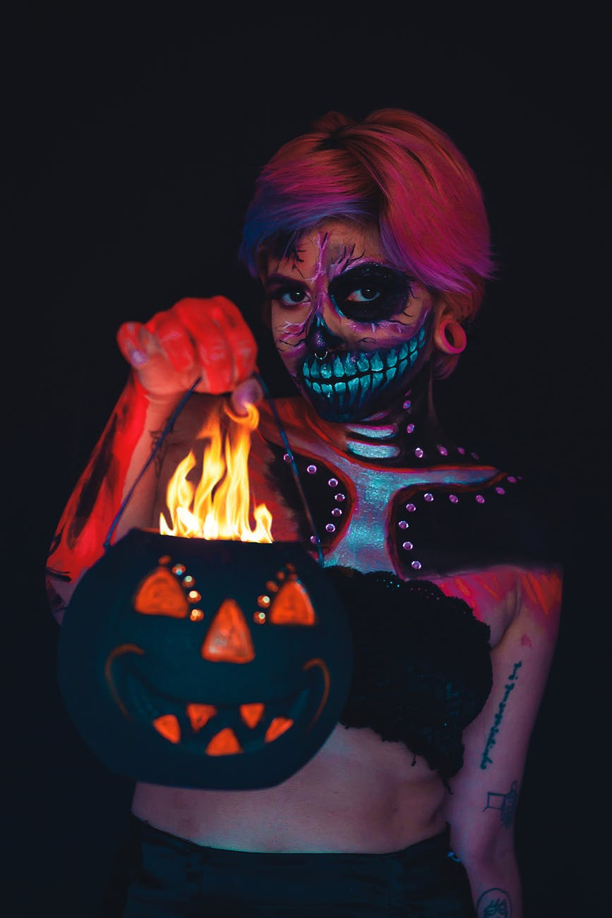 woman with a face and body painting holding a halloween pumpkin bucket