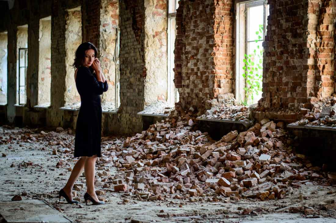 woman in black dress standing in front of pile of bricks