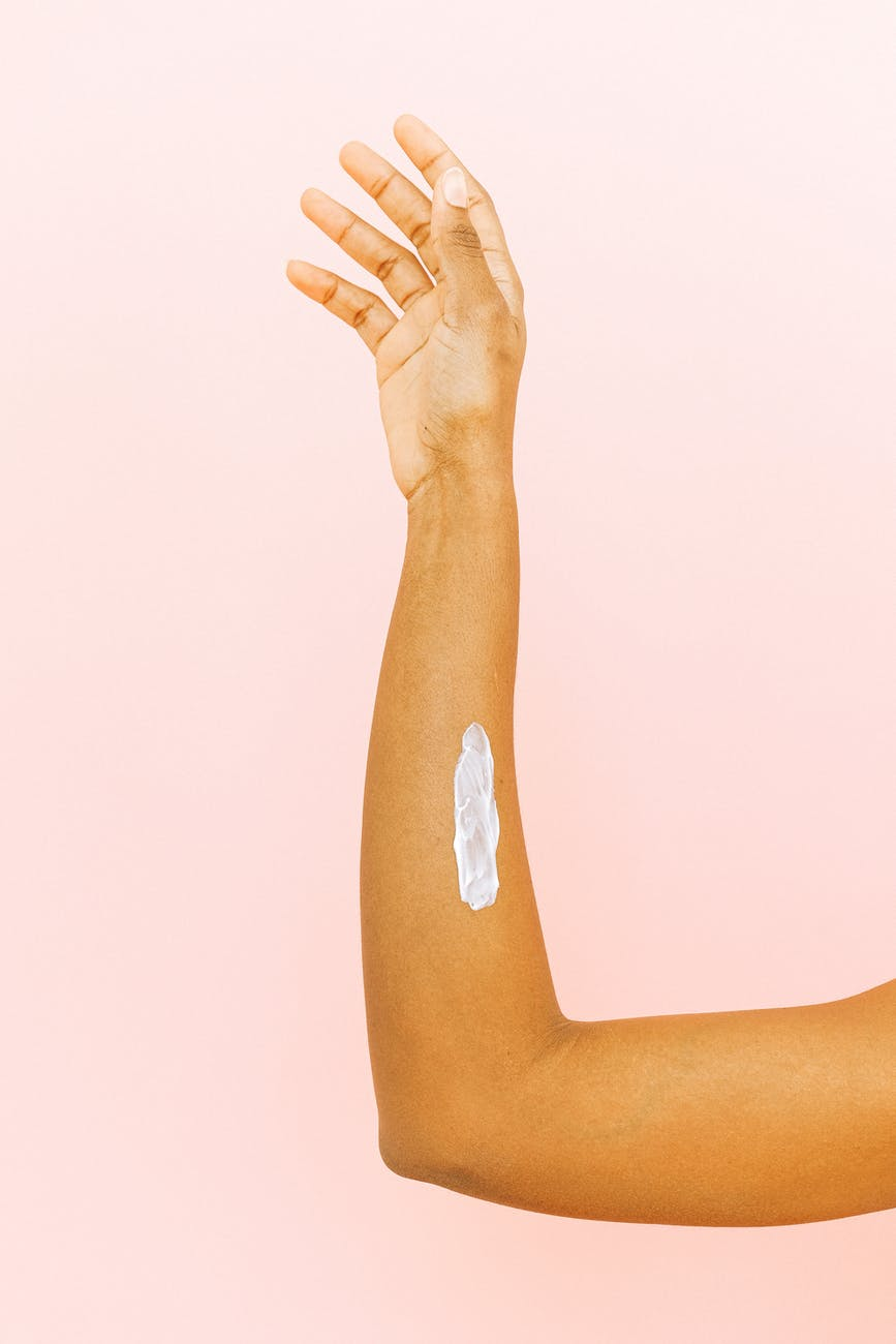 female arm with smear for skin care against pink background