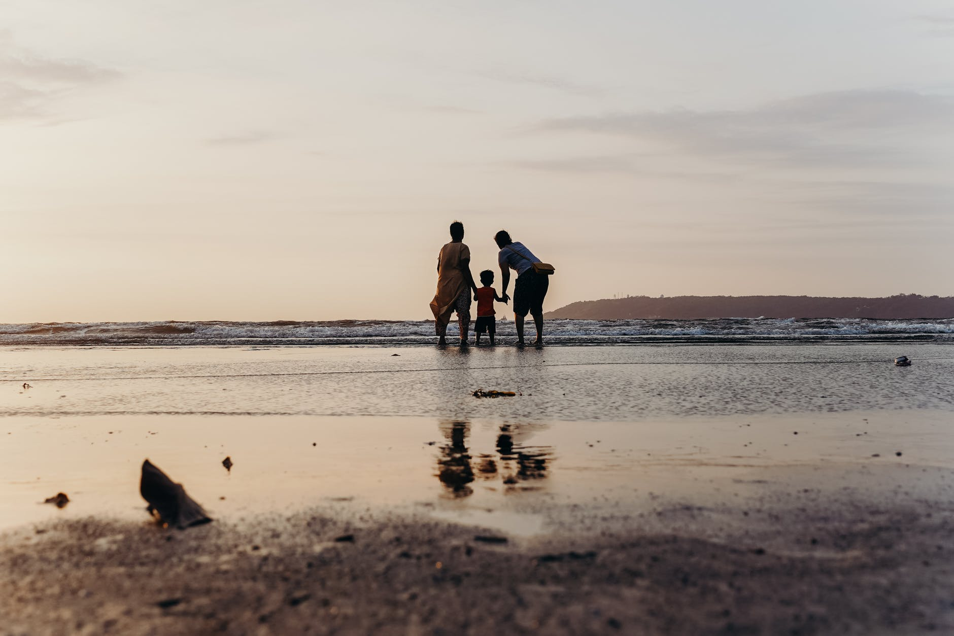 photo of three people standing on beach