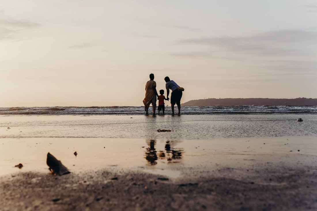 photo of three people standing on beach