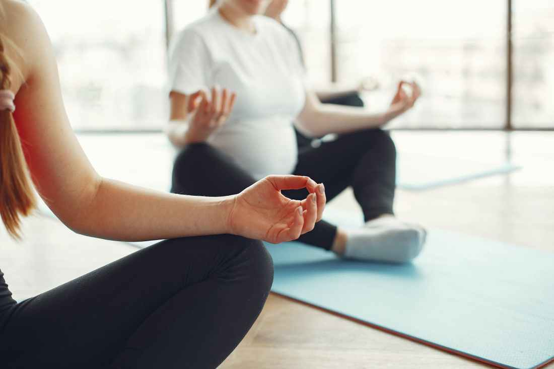 pregnant women meditating in fitness studio