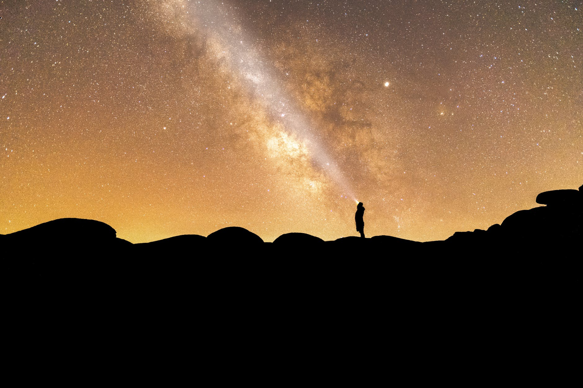 silhouette of person standing on rock formation under starry sky