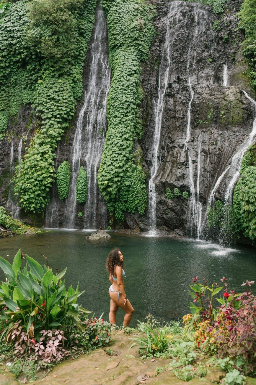 relaxed woman in swimwear enjoying day in rainforest near waterfall
